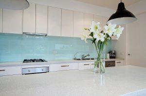 Kitchen installation with a blue glass splashback